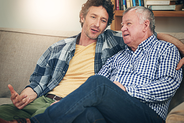Shot of a mature man and his elderly father sitting on the sofa at home and having a chat